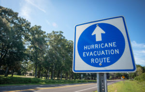 A sign next to a tree-lined road directs hurricane evacuees to safety.