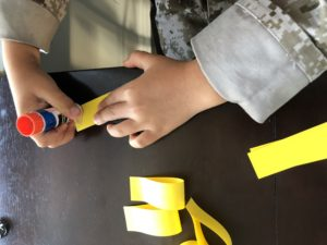 Gluing strips of paper for a sunflower craft
